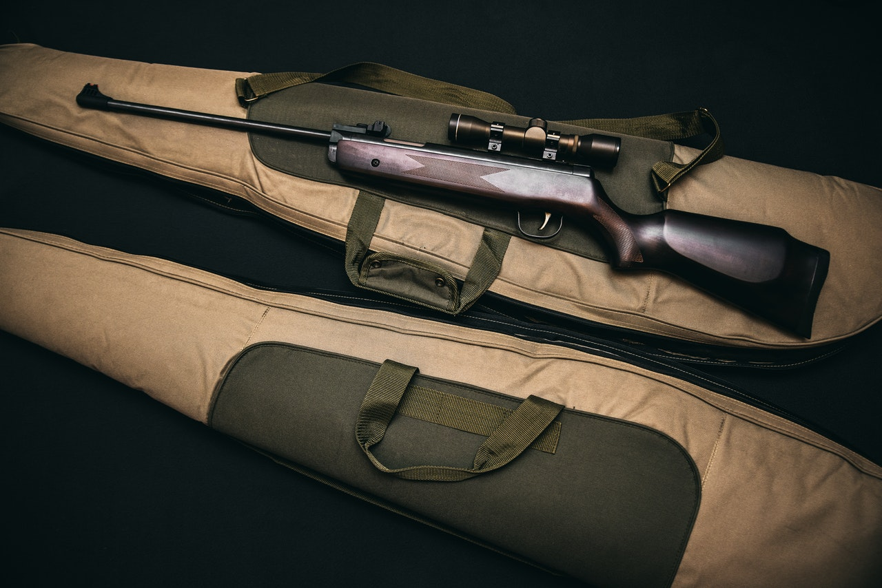 a rifle with a scope lying on top of a long firearm bag