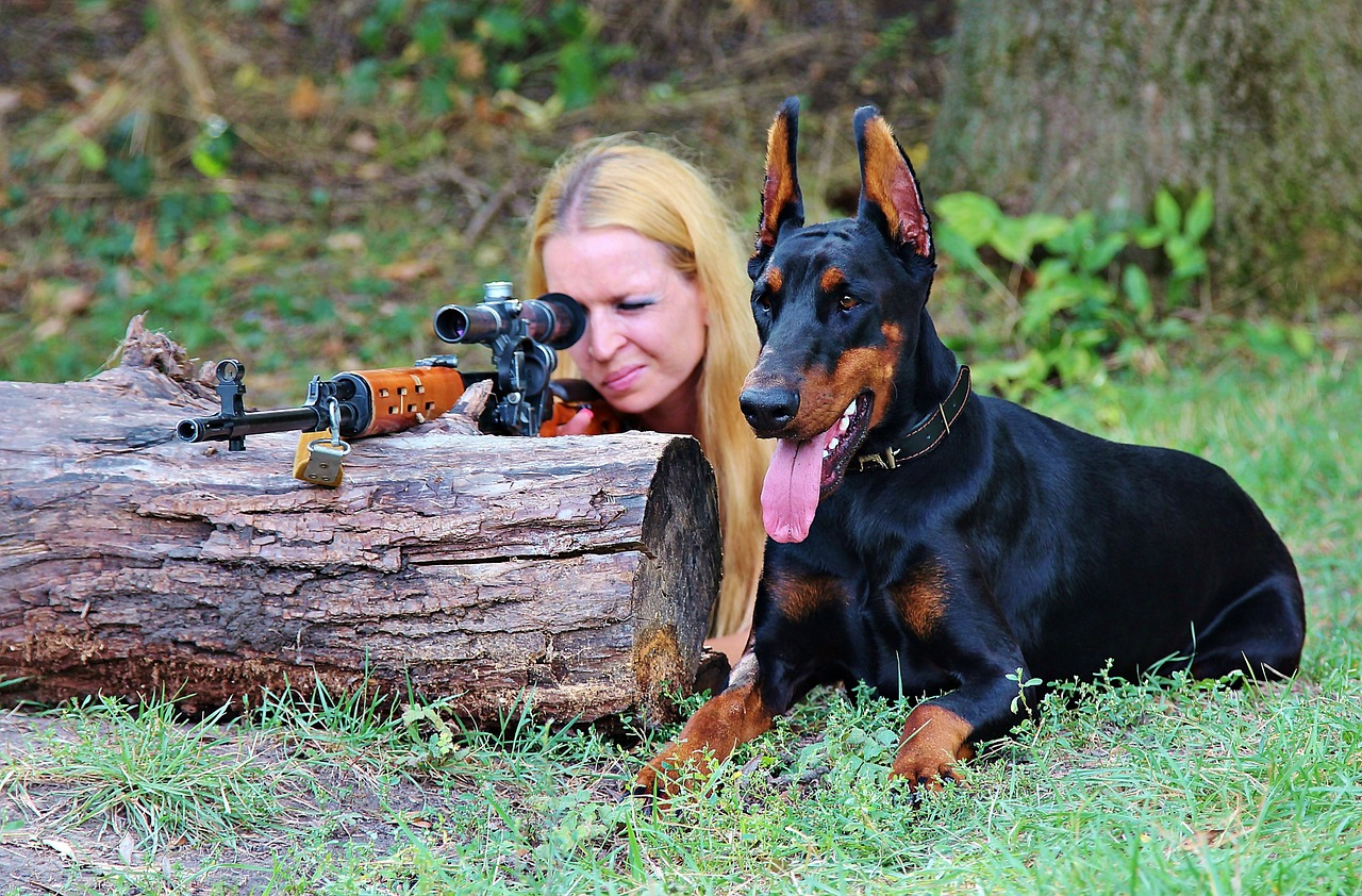 a woman sitting beside her hunting dog and aiming her rifle by looking through the scope