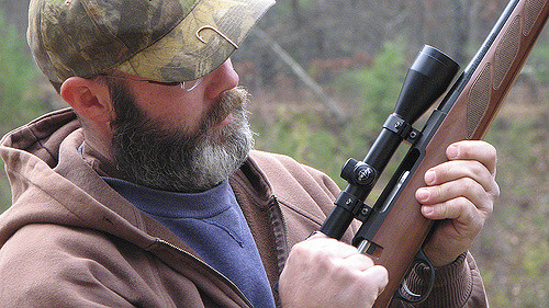 a man cocking his gun accessorized with the one of the best shotgun scopes