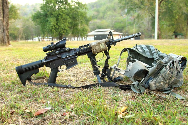 a rifle setup with a scope and bipod lying next to a camouflage backpack