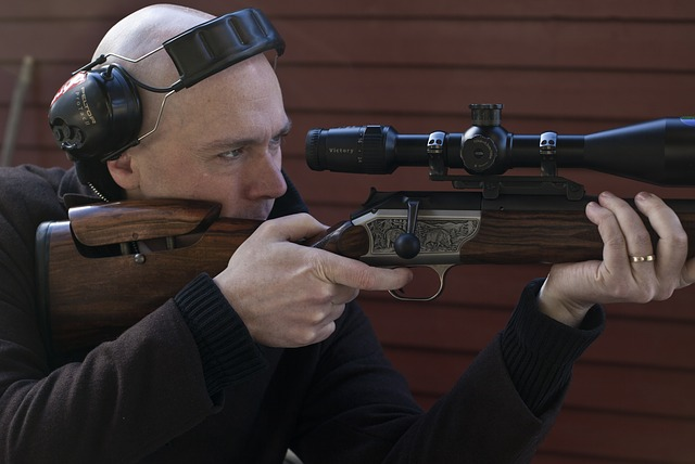 a man looking through the rifle scope as he aim his rifle to his target