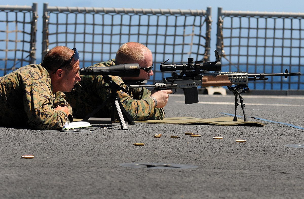 a navy aiming the target using a firearm with riflescope