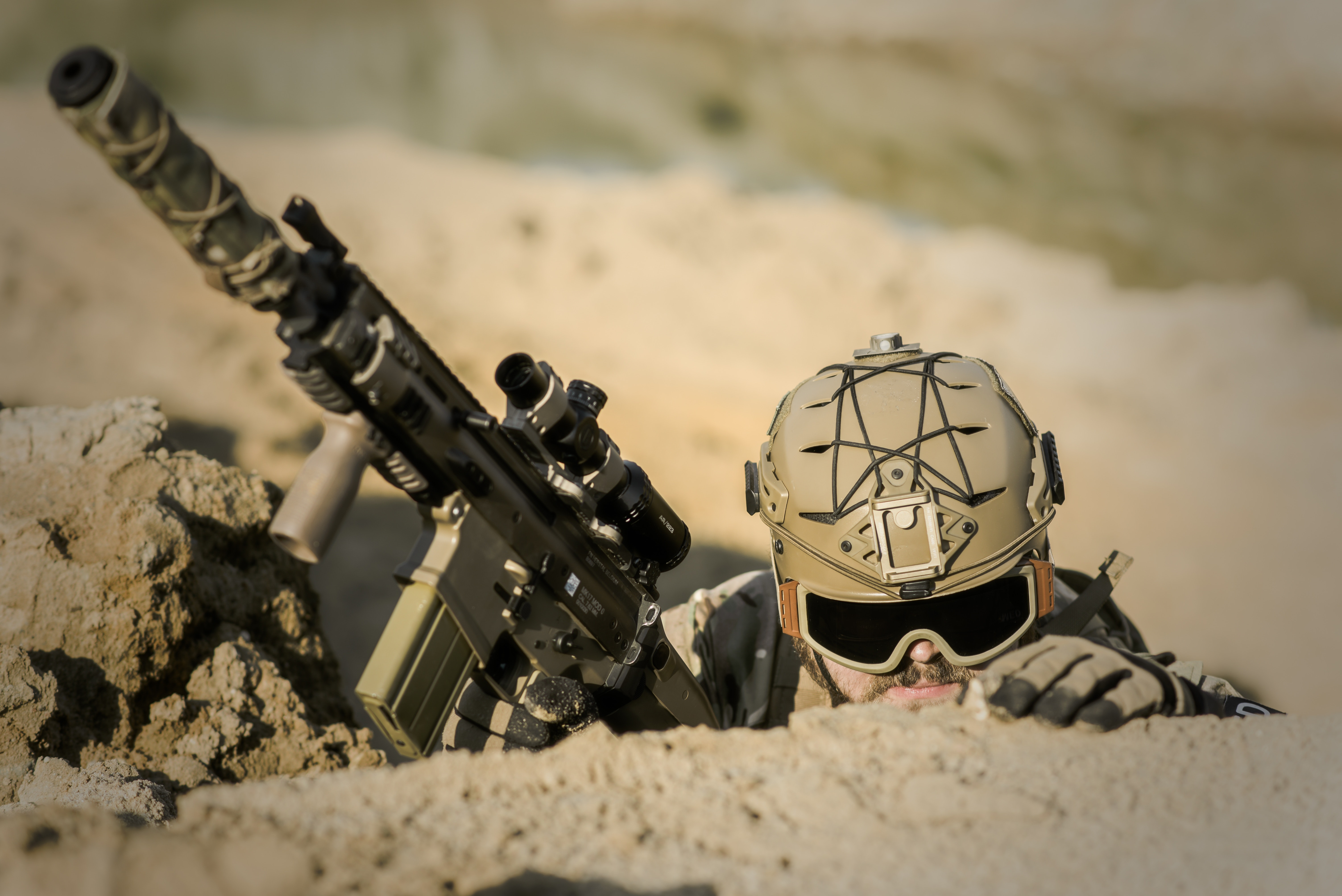 a soldier hiding and holding up a firearm with scope