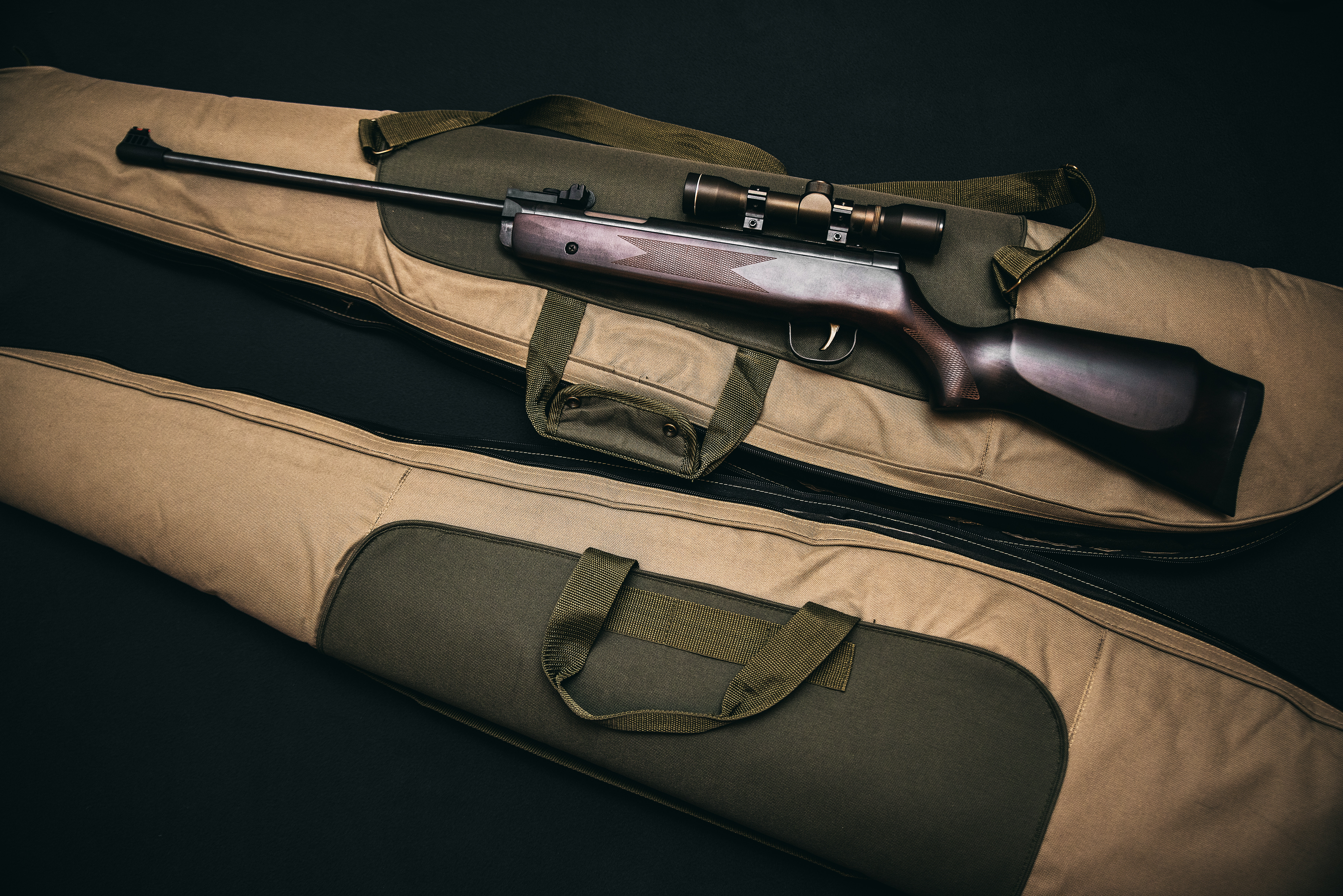 a rifle with scope on top of a rifle bag