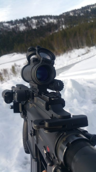 close-up photo of an automatic rifle with scope being used on a snowy environment