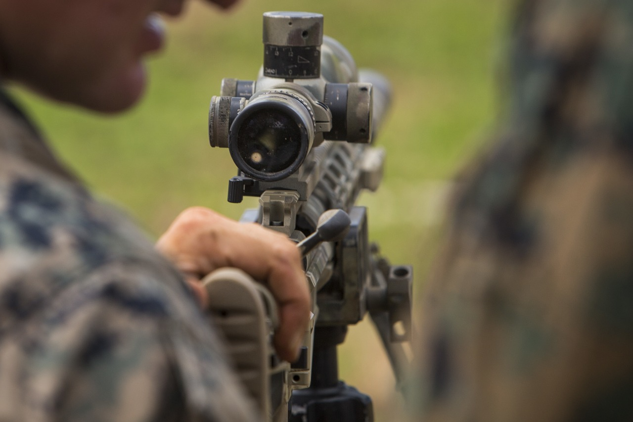 close-up photo focused on rifle scope attached to a gun used for target shooting