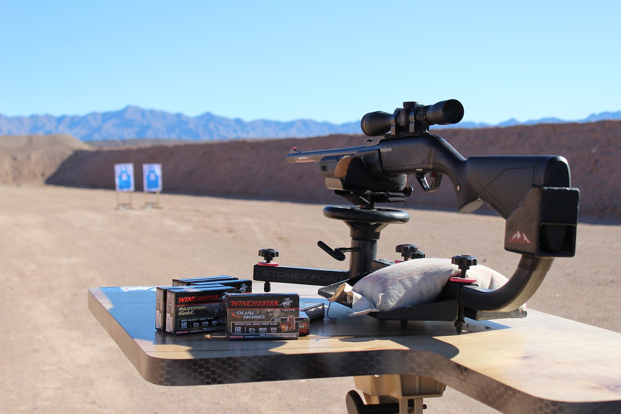 a rifle with attached rifle scope set up in an outdoor shooting range