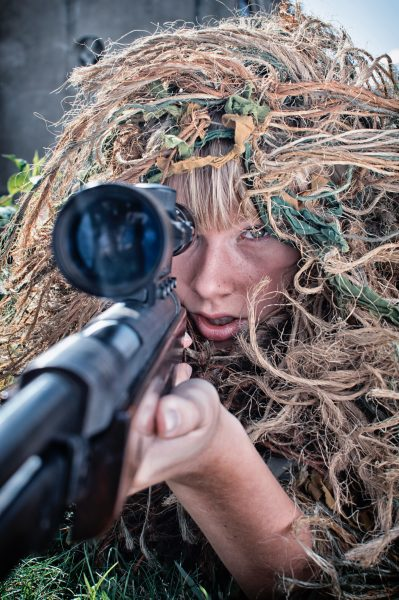a person wearing a camouflage cover in his head and holding up a gun with scope