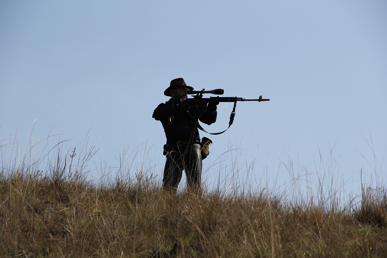 a man standing on a hill while holding up this gun and aiming at his target