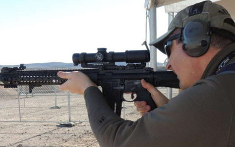 a man in target shooting practice, holding up a rifle and looking through the attached 1-4x scope