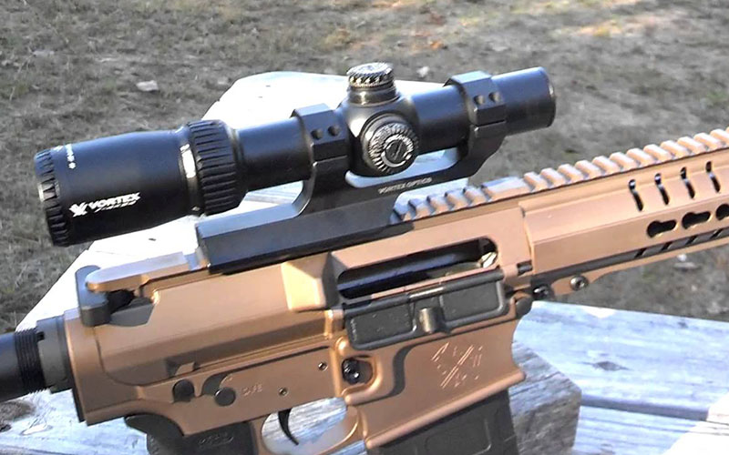 close-up photo of a 4x scope attached to a firearm