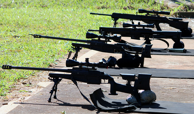 rifles with scopes attached lined up on the ground