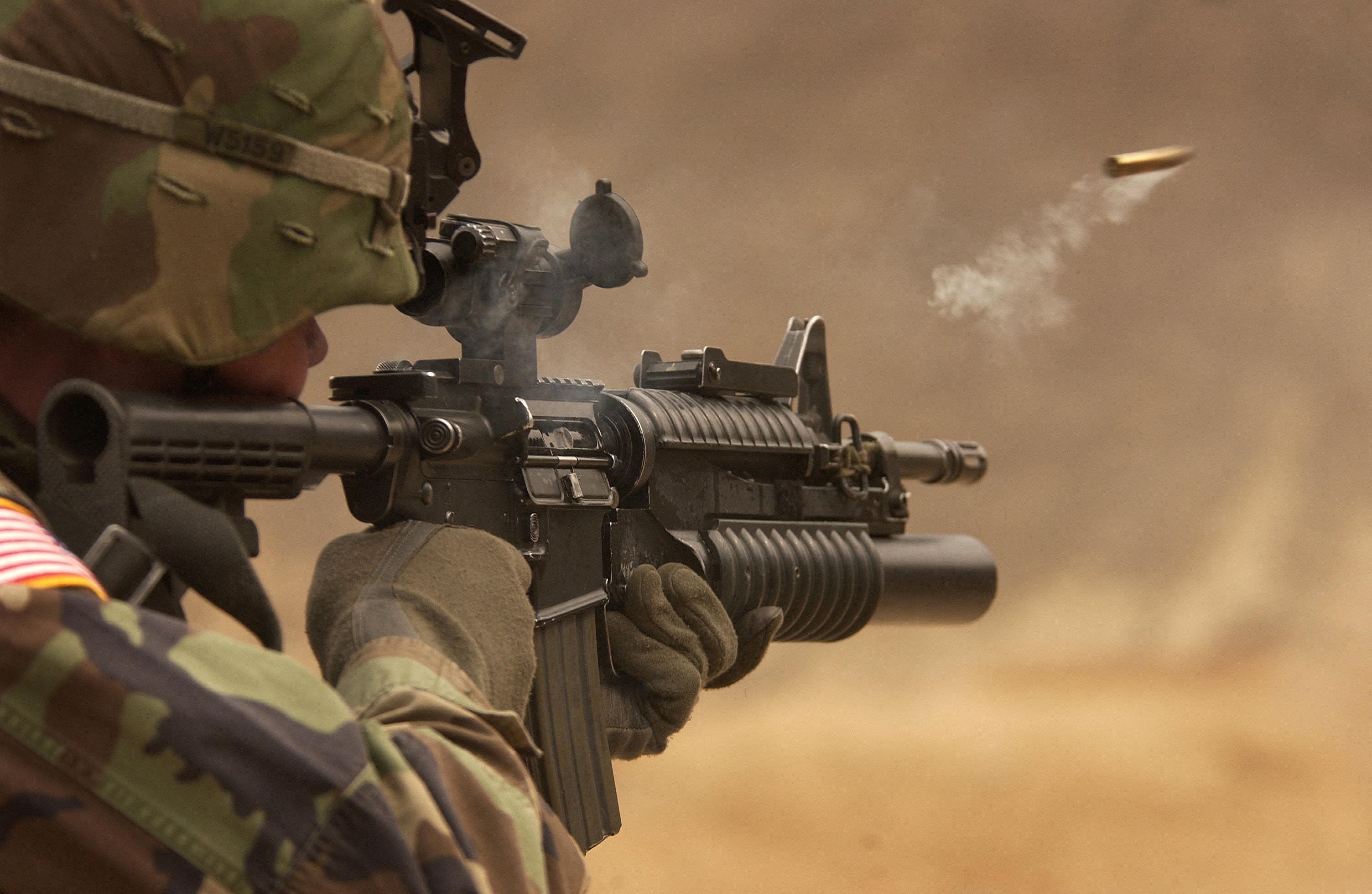 a soldier firing a firearm with attached scope