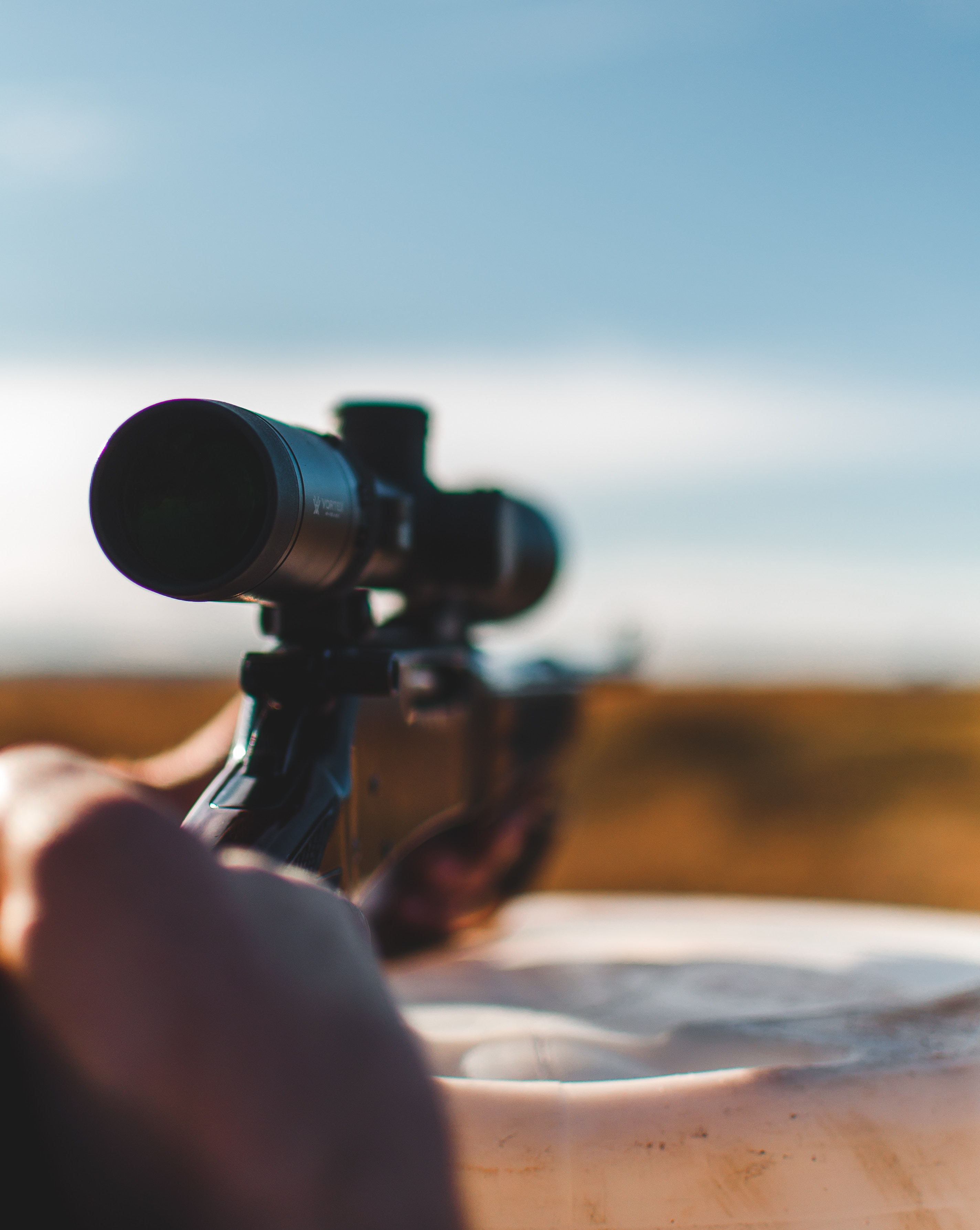 close-up photo focused on a 4x scope attached to a firearm being used during hunting activity