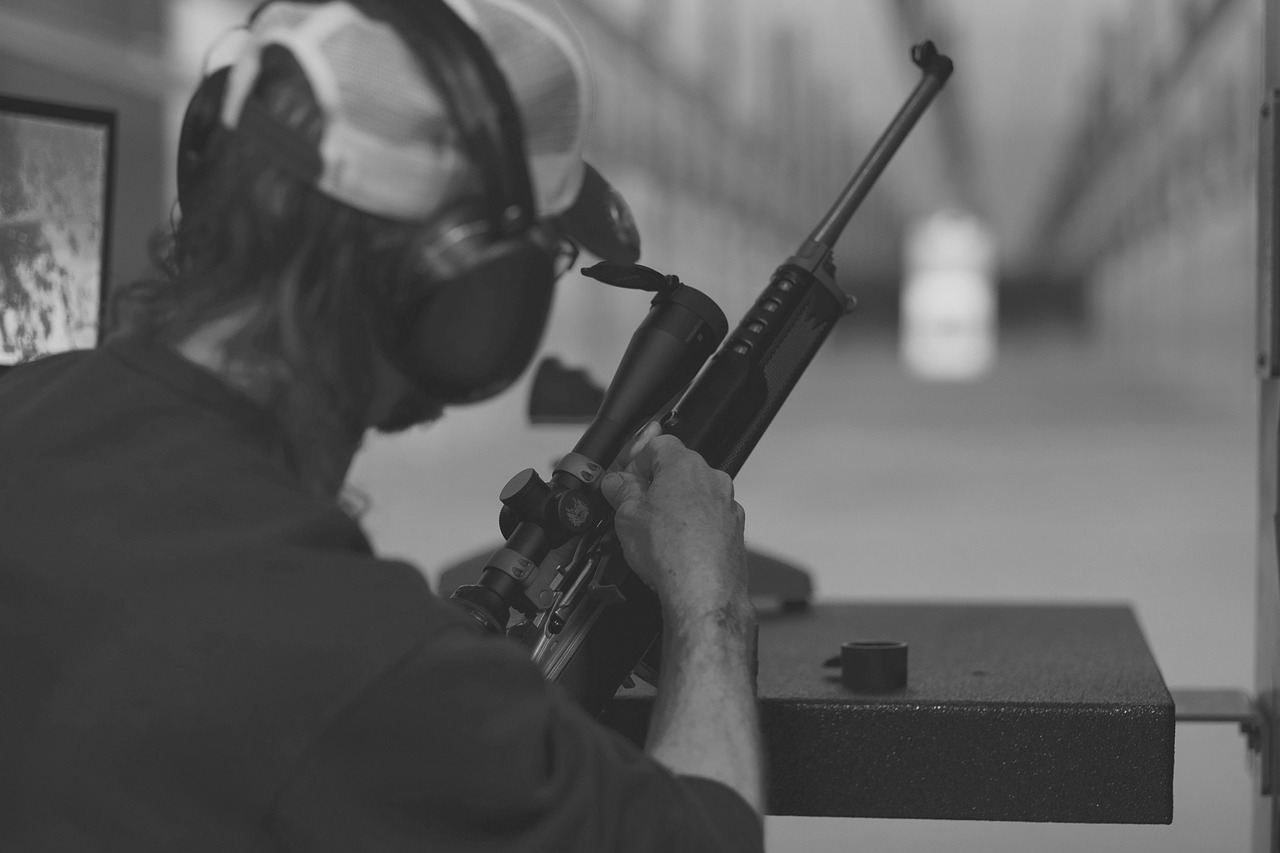 black and white photo of a man preparing to use a rifle with 4x scope during a target practice shooting
